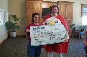 Harlan Berning, LPN, presents our check to the US92 Superhero.